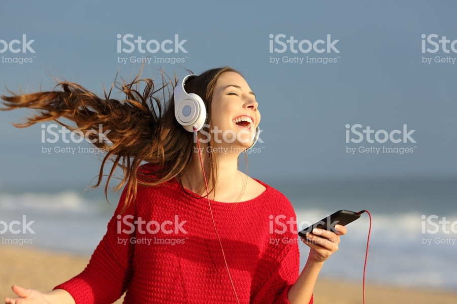 Happy girl dancing and listening music